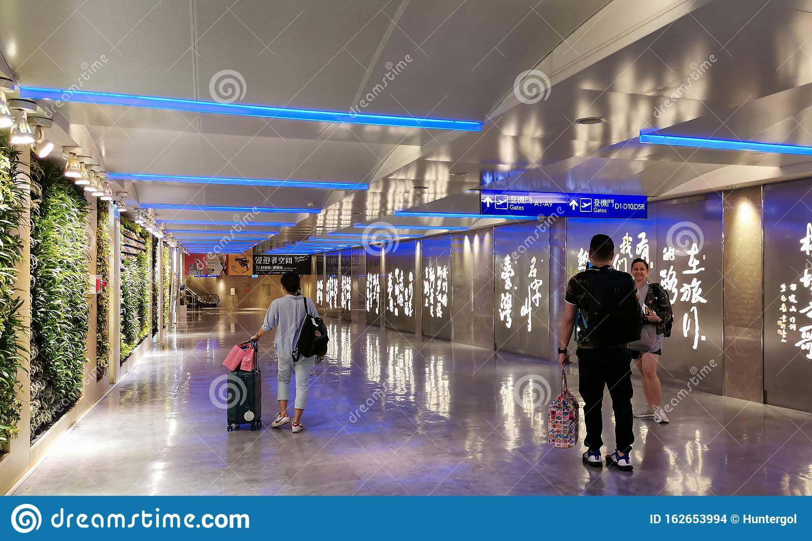 beautiful-walking-path-to-departure-gates-terminal-taoyuan-aiport-chinese-writing-one-wall-green-grass-other-side-162653994.jpg